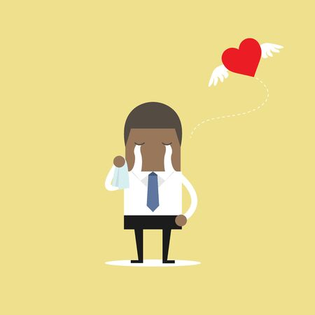 African businessman crying broken heart with heart flying away.