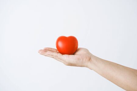 The hand of a man holding a red heart on white background.