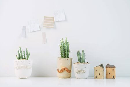 Succulents or cactus in clay pots plants in different pots. Potted cactus house plants with sticky note on white wall. Stock Photo - 138171939
