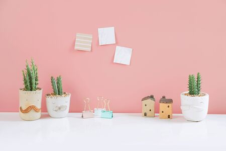 Succulents or cactus in clay pots plants in different pots. Potted cactus house plants with sticky note on pink wall.