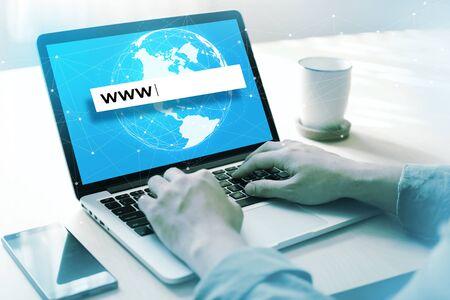 Mani dell'uomo d'affari che legano www nella casella di testo sul computer portatile con sfondo di connessione globale sullo schermo.