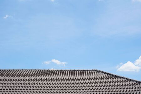 Black tile roof of construction townhouse with blue sky and cloud background.