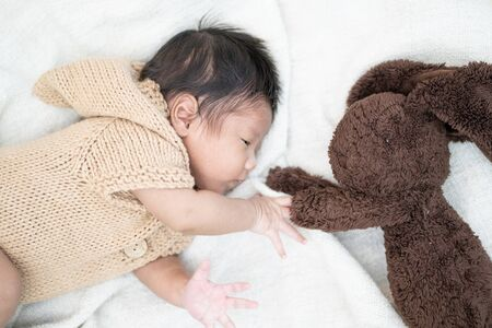 Adorable newborn baby peacefully sleeping with brown rabbit doll on a white blanket.