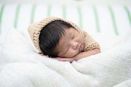 Aanbiddelijke pasgeboren baby die vreedzaam op een witte deken slaapt.
