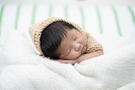 Adorable newborn baby peacefully sleeping on a white blanket.