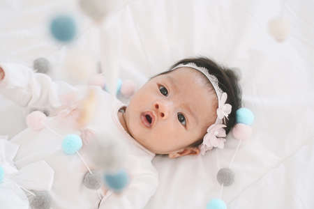 Adorable little baby girl in a beautiful dress watching baby crib mobile at home. Baby crib mobile. Toys above the baby crib. Hanging soft balls for the child.