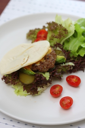 Beef burger with bun in white disk photo