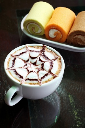 hot cappuccino, coffee in white cup and cream roll photo