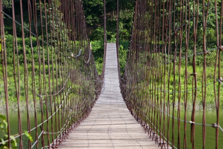 suspension bridge cross the resuvoir of earth dam at Phetchaburi province, Thailand. photo