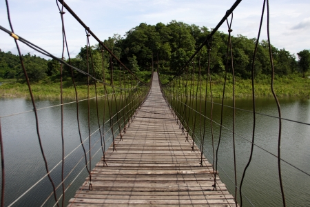 suspension bridge cross the resuvoir of earth dam at Phetchaburi province, Thailand. photo