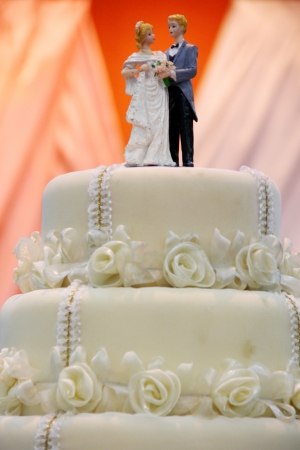 figurines of the bride and groom on traditional wedding cake photo