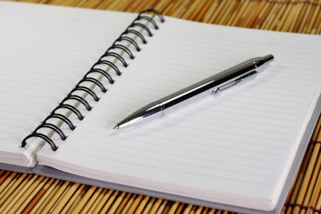 Notebook and silver pen on bamboo background. Stock Photo - 19472421