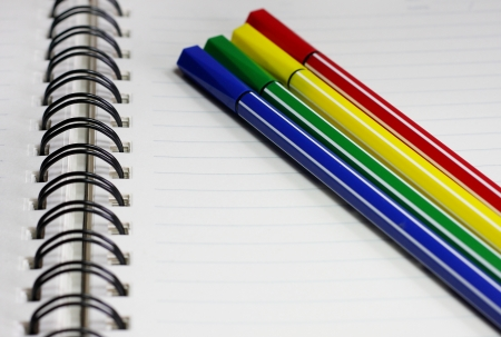 Notebook and color pen, blue, green, yellow and red. photo