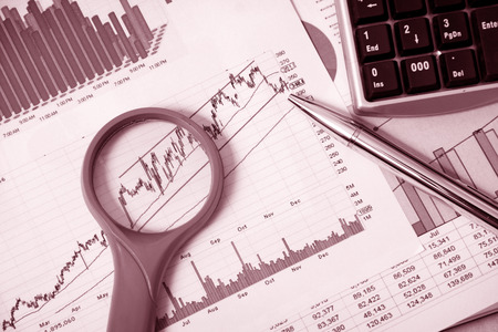 Business finance chart with magnifying glass and silver pen on table. photo