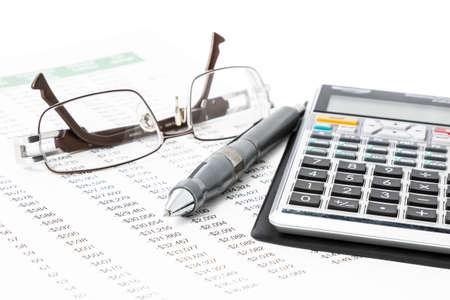 Een pen, een rekenmachine en glazen op een lijst met nummers Stockfoto