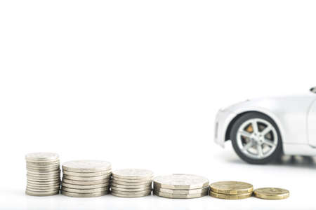 decreasing: stacked coins on a white background in decreasing heights with car in the background