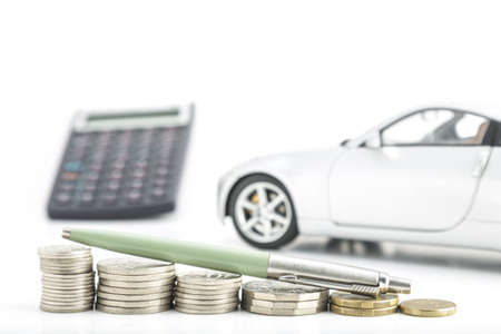 decreasing: stacked coins on a white background in decreasing heights with car and calculator in the background Stock Photo