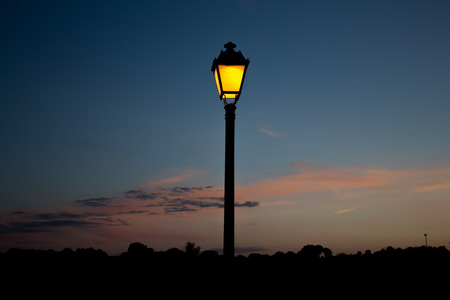 anticipating: The streetlamp iluminates the country side, anticipating the coming night