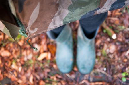 botas altas: Mujer en el impermeable y botas de pie en las hojas de otoño