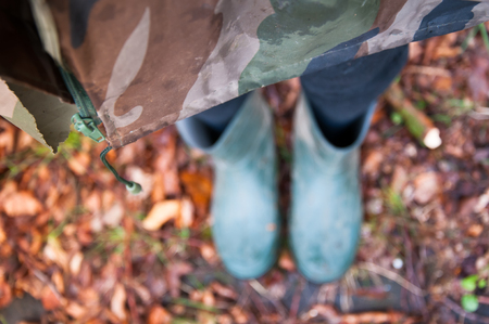 waders: Woman in raincoat and waders standing on autumn leaves