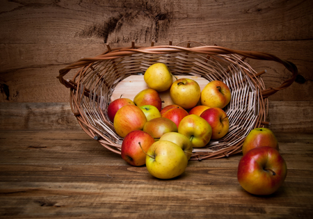 bushel: Apples sitting in a wooden basket on wooden background