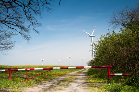wind force wheel: Wind turbine behind the barrier and trees Stock Photo