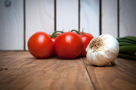 bulb and stem vegetables: Tomatoes and garlic on wooden table