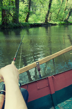 sportfishing: Hand holding a fishing rod with reel