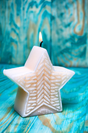 star shaped: Christmas star shaped candle on blue background
