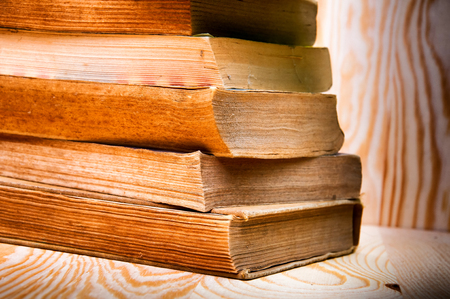 books on a wooden surface: Vintage antiquarian books pile on wooden surface