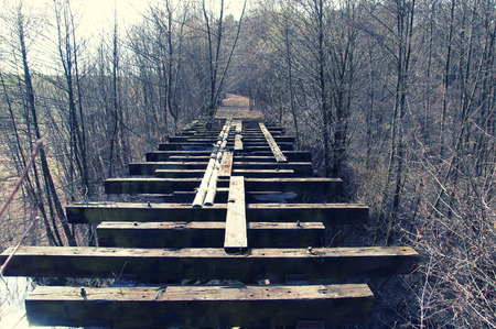 mood moody: Old abandoned wooden bridge in forest