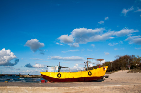 Yellow fishing boat moored on the beach
