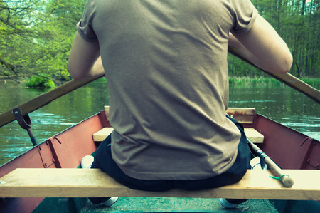 oar: Young man rowing with oar on the boat