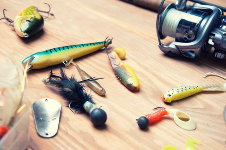 baits: Fishing baits and rod isolated on wooden background