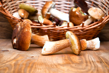Fresh mushrooms in basket on wooden table Stock Photo