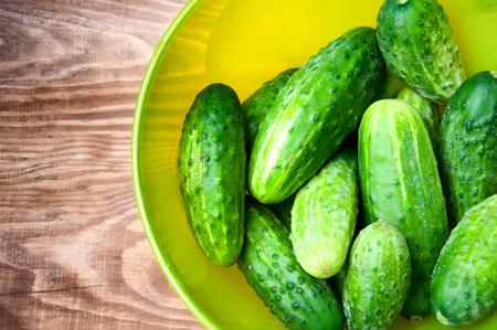 Mini cucumbers in bowl on table