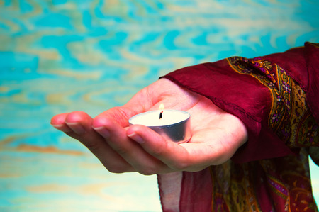 Oriental womans hands holding a tea light candle Stock Photo