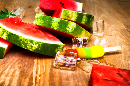 sliced watermelon: Pieces of watermelon and ice cream on wooden background Stock Photo