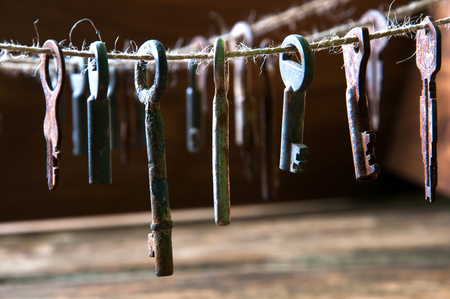 Old rusty keys hanging on a twine