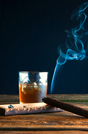 snifter: Whisky with ice and cigar on wooden table Stock Photo
