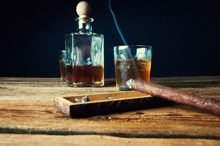 Cigar and whisky with ice on wooden table Stock Photo