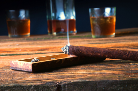 snifter: Cigar and whisky with ice on wooden table Stock Photo