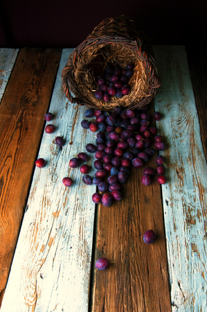 falling out: Purple plums falling out of the basket on white and brown table Stock Photo