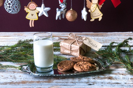 milk and cookies: Milk, cookies and some gift for Santa Stock Photo