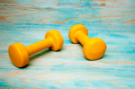 Yellow dumbbells 1kg on blue wooden background