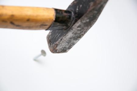 Studio isolated hammer hitting a nail