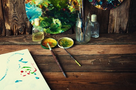 watercolor paper: Palettes, brushes and canvas in an old painting workshop Stock Photo