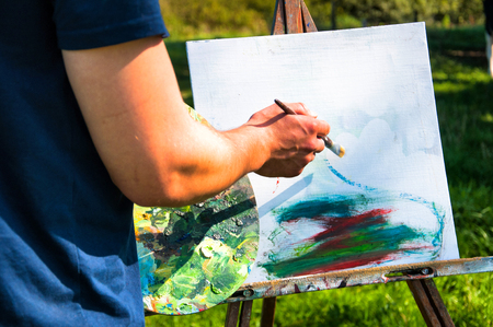 Man painting a picture in the open air