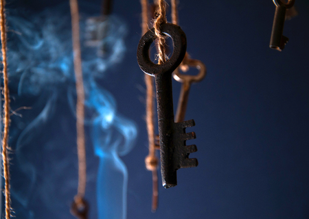 Keys hanging on a string. Smoke background. Selective focus Stock Photo
