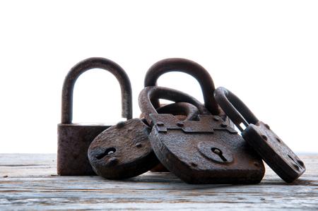 Old rusty padlocks on white wooden table Standard-Bild